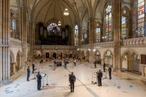 """Das Bild zeigt das Innere der Peterskirche in Leipzig, in dem der MDR-Rundfunkchor das Werk """"Inseln"""" augenommen hat. Die Sänger*innen stehen mit großem Abstand in der leeren Kirche."""