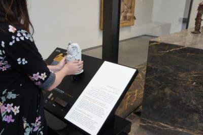 Eine Person am linken Bildrand legt ihre Hände auf ein taktiles Ausstellungsobjekt
