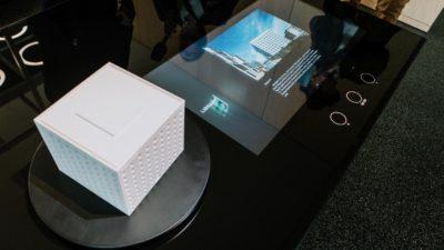 Ein Tastmodell eines Gebäudes steht neben einer digitalen Anzeige.