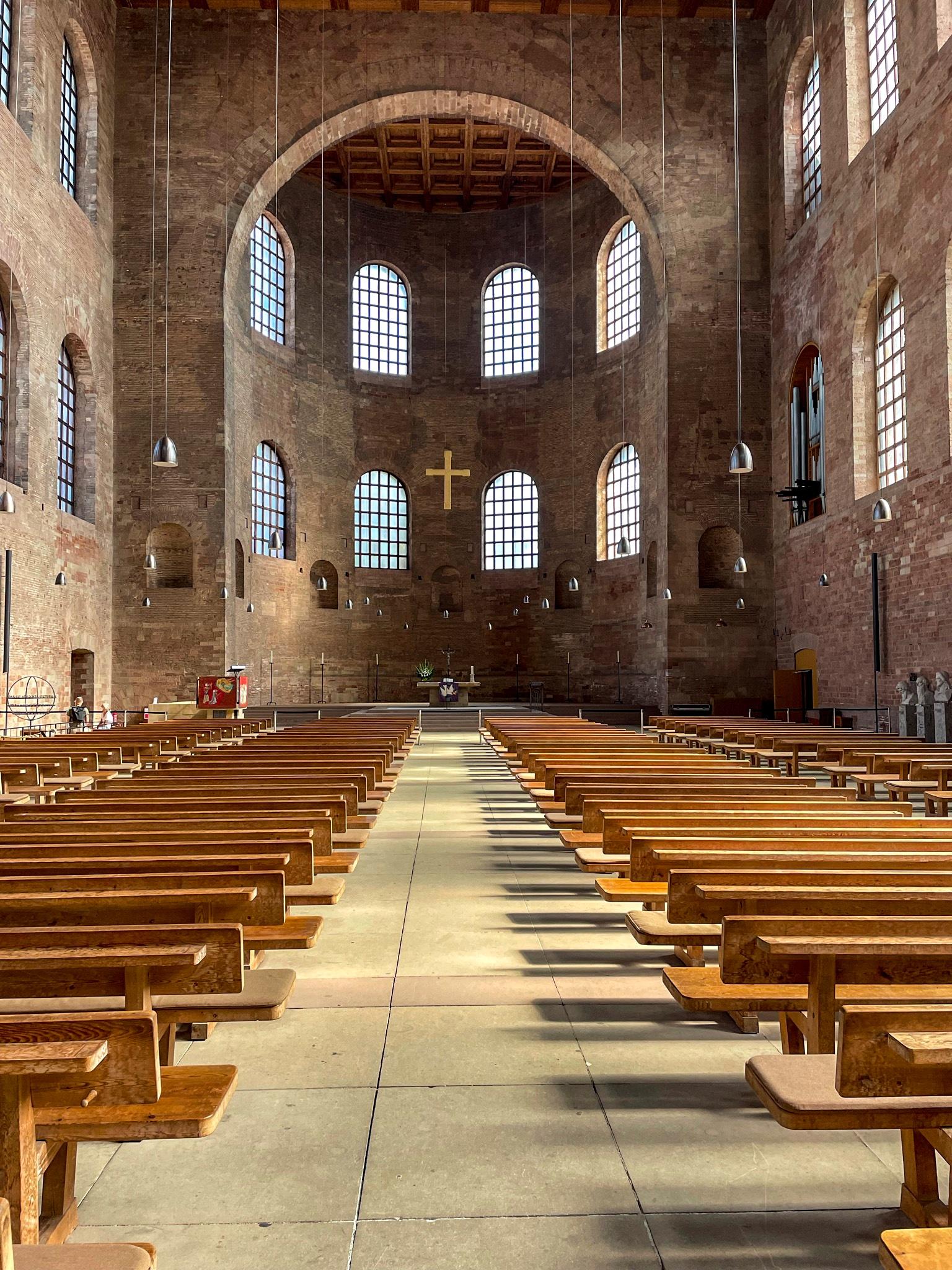 Innenraum des Kirchenschiffs der Konstatinbasilika in Trier. Licht fällt von rechts durch die Kirchenfenster auf die Kichrnbänke.
