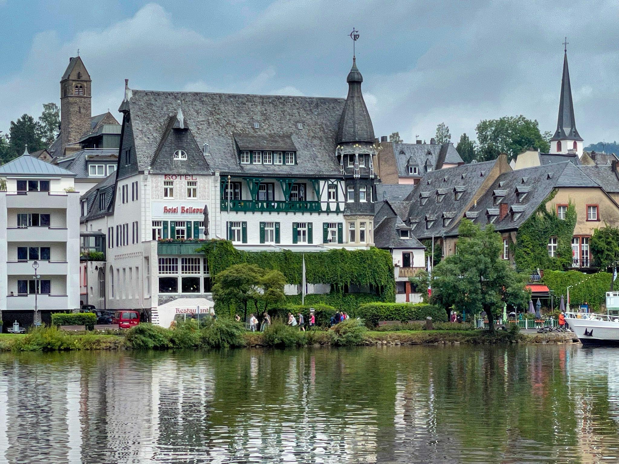 Blick über einen Fluss auf ein klissizistisches Hotel mit Türmchen