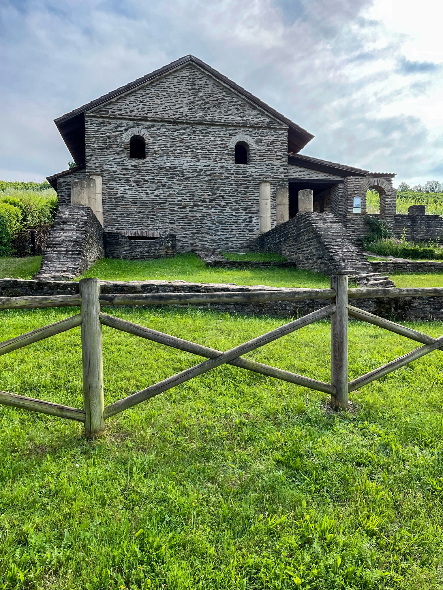 Frontaler Blick auf eine römische Landvilla, umgeben von grüner Wiese.